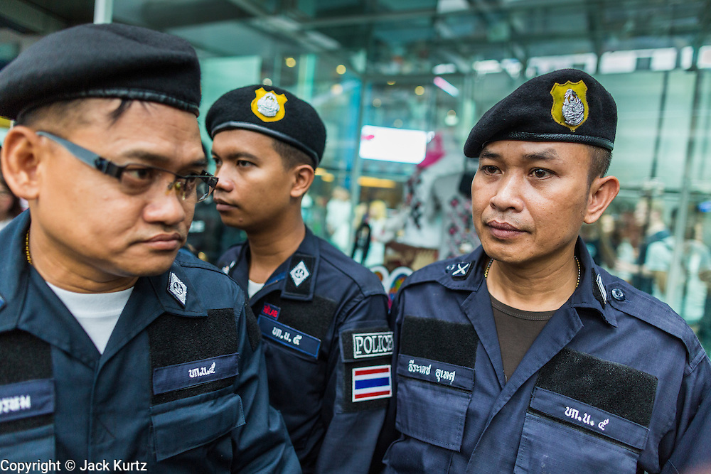 "01 JUNE 2014 - BANGKOK, THAILAND: Thai police patrol near the Asok BTS Skytrain station in Bangkok after a flash mob protested against the coup near the station. The Thai army seized power in a coup that unseated a democratically elected government on May 22. Since then there have been sporadic protests against the coup. The protests Sunday were the largest in several days and seemed to be spontaneous ""flash mobs"" that appeared at shopping centers in Bangkok and then broke up when soldiers arrived. Protest against the coup is illegal and the junta has threatened to arrest anyone who protests the coup. There was a massive security operation in Bangkok Sunday that shut down several shopping areas to prevent the protests but protestors went to malls that had no military presence.    PHOTO BY JACK KURTZ"