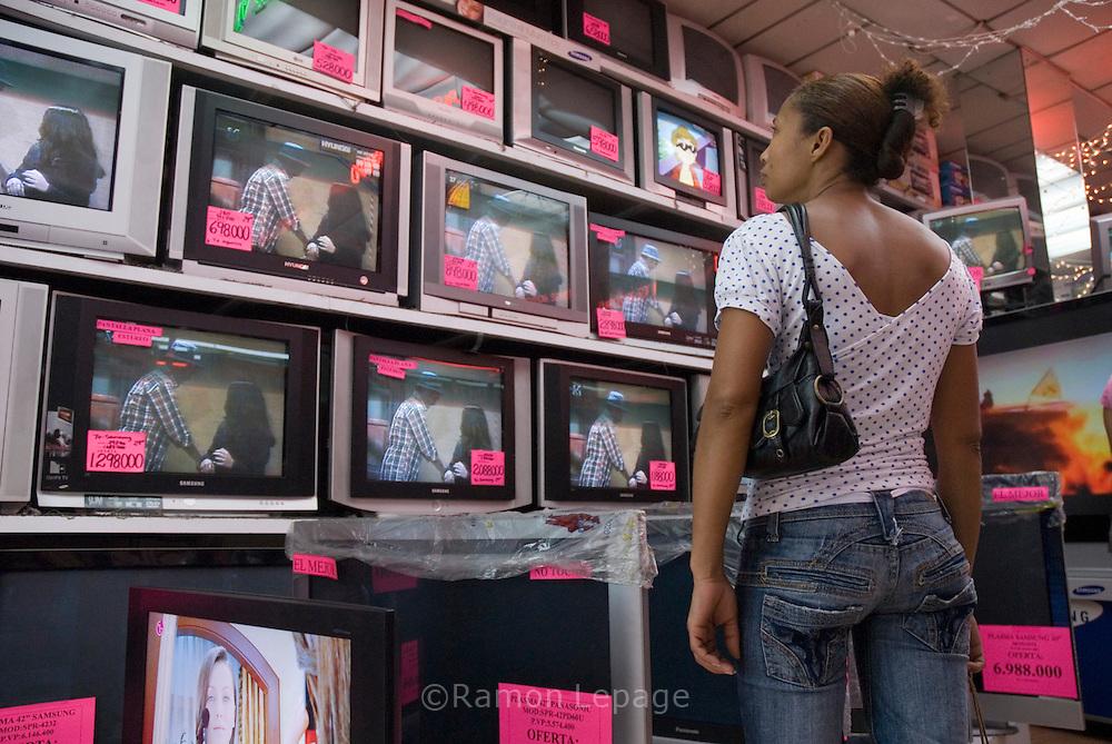 Consumidores venezolanos compran electrodomésticos y otros productos en la tienda Marttel de Caracas. Muchas personas compran bienes debido al gran flujo de gastos de gobierno, créditos bancarios privados y el miedo a la inflación.  Uno de los hechos económicos más importantes, en estos años, ha sido el control monetario impuesto por la administración de Chávez, colocando el precio del dólar a 2150 bolívares mientras que en el mercado negro se vende de 3500 a 4200 bolívares, y limitando el cupo de consumo en gastos electrónicos y de viajes. Caracas, 6-03-07 (Ramón Lepage/Orinoquiaphoto)  Venezuelan consumers shopping for electronic and home appliances at Marttel store in Caracas, March 06, 2007. Many people are buying goods due to the large cash flow from government spending, enticing private bank loans and also fears of inflation in the economy. The Chavez adminitration implemented more than 3 years ago a currency control, setting the the price of 2150 bolivares per dollar while the black market price is about 3500 to 4200 bolivares. Venezuelans are allowed to spend during the year up to  $ 5000 for travel and $3000 for internet shopping. (Ramón Lepage/Orinoquiaphoto)
