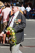 Old Soldier marches with flower wreath during Brisbane ANZAC day 2005 parade