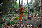 Novice monks sweeps leaves up at their residence as part of their daily chores in the Monks Community Forest.