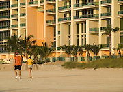 Two people jogging on the beach with a large new hotel in the background Miami Beach USA.