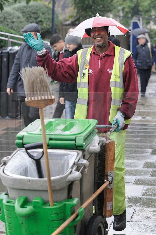 &copy; Licensed to London News Pictures. 11/10/2013<br /> Wet rainy weather today (11.10.2013)  Tower Hill,London. <br /> This Tower Hamlets street cleaner named Omar is enjoying the rain with his head umbrella on as he works outside Tower Hill Station,London.<br /> Photo credit :Grant Falvey/LNP