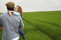 Father embracing daughter (5-6) in field
