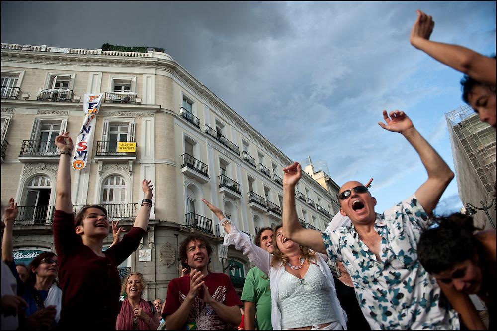 """Un groupe de manifestants dansent en cercle autour d'un musicien aux abords du camp. // Le mouvement spontane du """"15 M"""" (15 mai) compose de citoyens espagnols campe depuis 2 semaines sur la place Puerta Del Sol avec pour revendication la construction d'une democratie nouvelle. Organise en commission les citoyens prennent la parole lors d'assemblee ouverte a tous - Place Puerta Del Sol à Madrid le Juin 2011. ©Benjamin Girette/IP3Press"""