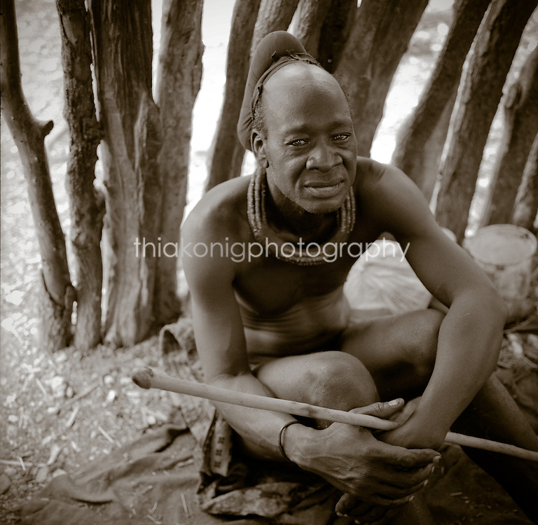 Black and white portrait of the headman of an Akha vilage, inside his stick hut, Northern Namibia, Africa