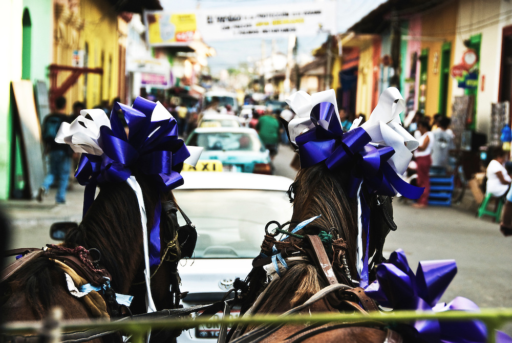 Horses join cars, motos, pedestrians, and bicycles in the busy streets of Granada, Nicaragua.
