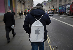 © Licensed to London News Pictures. 23/12/2016. London, UK. A shopper carries a bag from the Apple Store as he looks for last minute bargains at Oxford Circus on the last working day before Christmas. Photo credit: Peter Macdiarmid/LNP