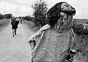 An individual wearing a mask and hessian clothing walks along a path with can in hand, Glastonbury 1998