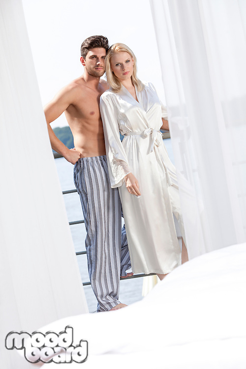 Portrait of loving young couple in sleepwear at hotel balcony