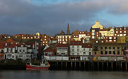 © Licensed to London News Pictures. <br /> 15/03/2015. <br /> <br /> Whitby, United Kingdom<br /> <br /> Morning sunlight reflects off houses in Whitby Harbour in North Yorkshire.<br /> <br /> Photo credit : Ian Forsyth/LNP