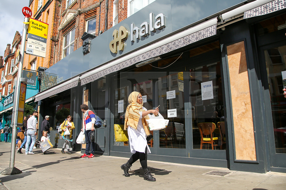 """© Licensed to London News Pictures. 24/05/2020. London, UK. A Muslim woman walks past ''HALA' a Turkish restaurant on Green Lanes, Haringey in north London which is open for take away only due to coronavirus lockdown, as Muslims celebrate Eid al-Fitr. On Eid al-Fitr also known as """"Festival of Breaking the Fast"""", a religious holiday celebrated by Muslims worldwide that marks the end of the month-long fasting of Ramadan, restaurants would normally be packed with people celebrating Eid. Photo credit: Dinendra Haria/LNP"""