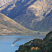 The TSS Earnslaw,  a 1912 Edwardian vintage twin screw steamer on the waters of Lake Wakatipu in, Queenstown, New Zealand. .It is one of the oldest tourist attractions in Central Otago, and the only remaining passenger-carrying coal-fired steamship in the southern hemisphere..The TSS Earnslaw heads along Lake Wakatipu from Queenstown  daily, running tourist trips to Walter Peak Station passing magnificent  peaks and contrasting shoreline foliage along the lakeside. Queenstown, New Zealand. 12th April 2011. Photo Tim Clayton