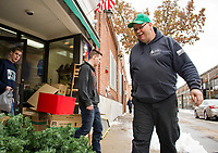 Derek, Nate and Jim Daubenspeck bring out garland for Christmas decorating in downtown Laconia on Saturday.  (Karen Bobotas/for the Laconia Daily Sun)