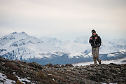 Woman hiking on ridge with mountains of The Alaska Range in the background, Denali National Park, Alaska