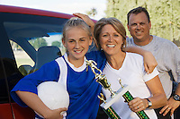 Parents with daughter (13-17) holding soccer trophy portrait