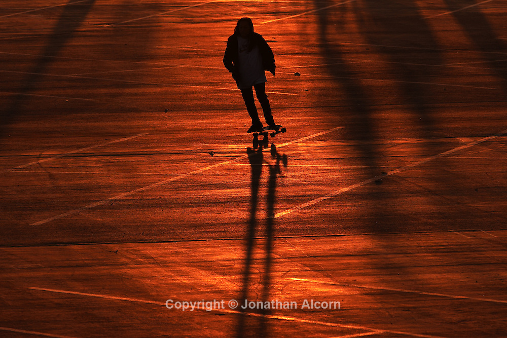Skateboarding across an empty parking lot that reflects the orange glow of sunset