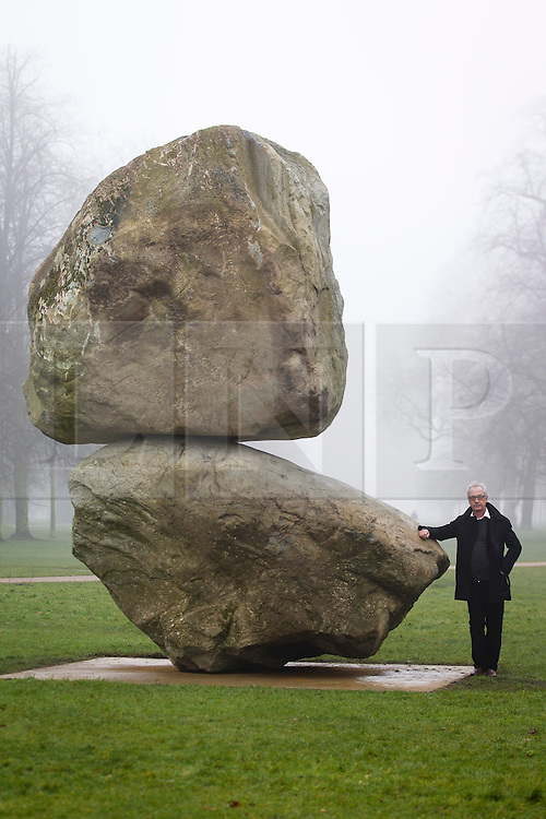 © Licensed to London News Pictures. 08/03/2013. London, UK. Swiss artist Peter Fischli poses with a giant boulder sculpture entitled 'Rock on Top of Another Rock' that he created with the late David Weiss outside the Serpentine Gallery in London, today (08/03/2013). The installation, which was unveiled today, is the first sculpture by the artists - Peter Fischli (b. 1952) and David Weiss (1946-2012) to be presented in the UK.  Photo credit: Matt Cetti-Roberts/LNP