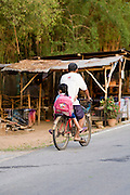 20 FEBRUARY 2008 -- KANCHANABURI, THAILAND: A man takes his daughter to school on the back of his bicycle in Kanchanaburi, Thailand.  Photo by Jack Kurtz