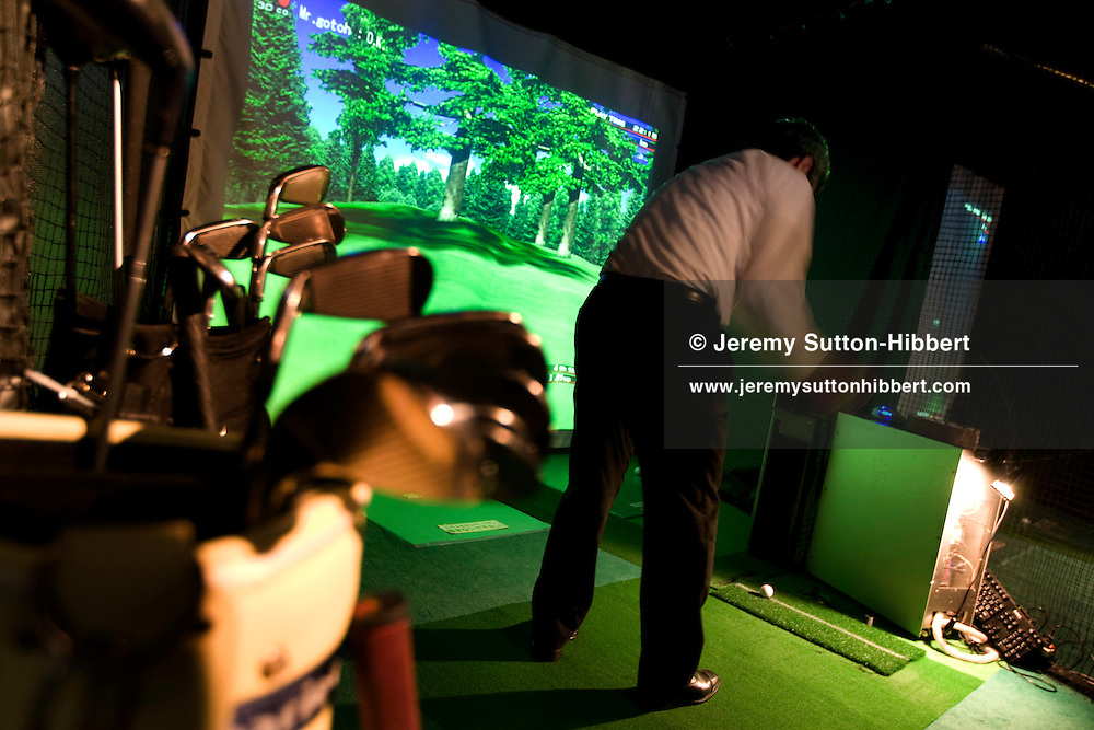 Japanese salarymen customers drink beers and play computerised golf, hitting balls at a screen which measures speed, direction and distance, in the 'Links Golf Bar', in Hamamatsucho, Tokyo, Japan. Wednesday, April 30th 2008.