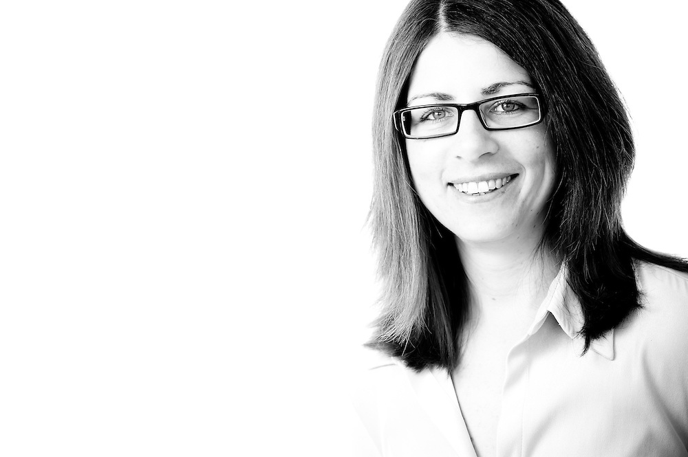 A pretty dark haired women with glasses smiling in black and white