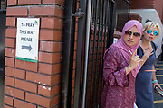 Following the attack on a group of Muslim men outside the Finsbury Park mosque which killed one person and seriously injured another ten, a Muslim lady stands alongside a sign pointing to where others can enter the Islamic building to pray during disruption, on 19th June 2017, in the borough of Islington, north London, England.