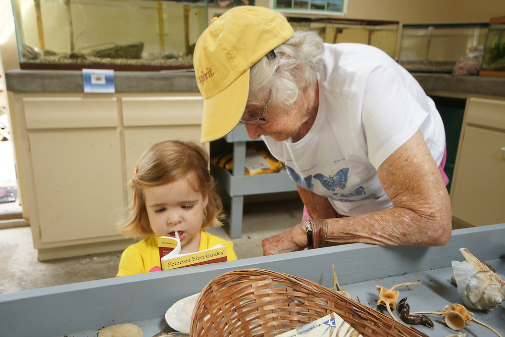 Child and grandmother with child reading at seashore museum, Cape May