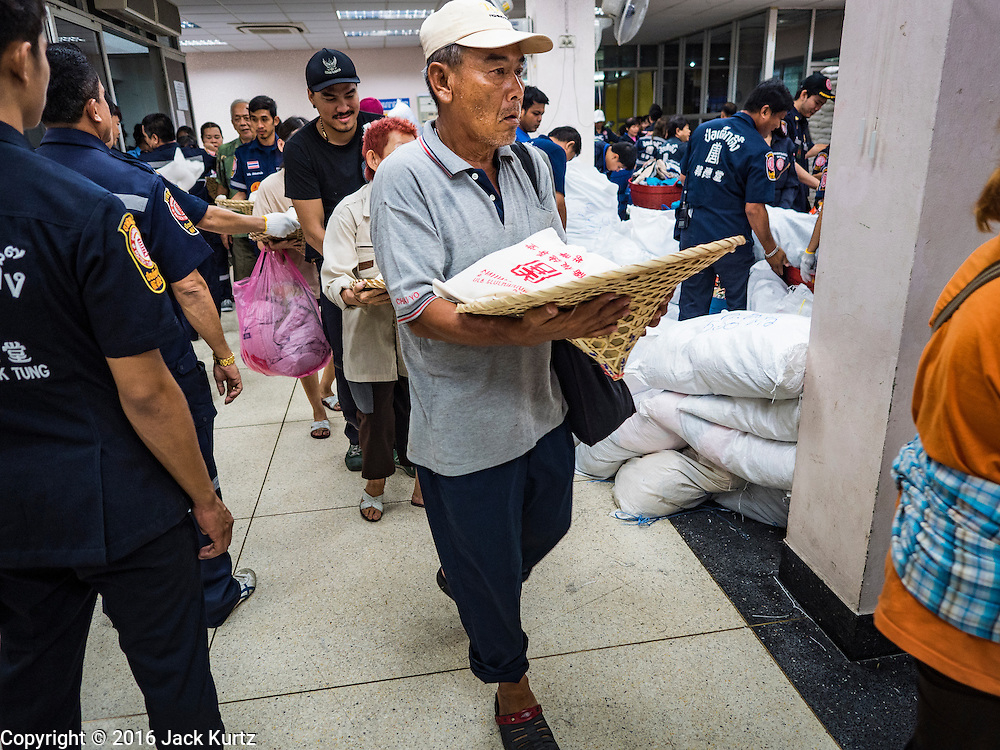 30 AUGUST 2016 - BANGKOK, THAILAND: People get food and clothing from volunteers at the Poh Teck Tung shrine on the last day of Hungry Ghost Month in Bangkok. Chinese temples and shrines in the Thai capital host food distribution events during Hungry Ghost Month, during the 7th lunar month, which is usually August in the Gregorian calendar.          PHOTO BY JACK KURTZ
