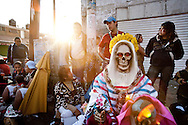 Devotees of Sante Muerte wait behind thier statutes at a montly Rosary ceremony in Tipito, Mexico City.