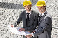 Portrait of confident young businessmen in hard hats examining blueprint outdoors
