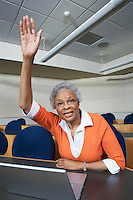Mature female student raising hand in lecture theatre