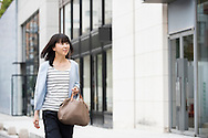 Mid adult attractive Japanese woman walking through the shopping district of Omatesando in Tokyo, Japan. Candid portrait of Asian female in urban street looking at shops.