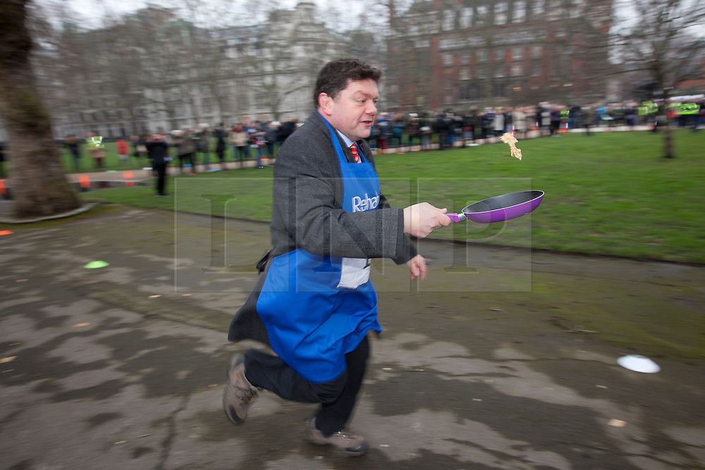 © Licensed to London News Pictures. 12/02/2013. London, UK. British Lord, Lord Addington, tosses a pancake as he takes part in the annual Rehab Parliamentary Pancake Race in Westminster, London today (12/02/2013).The race involving MPs from the House of Commons, Lords from the House of Lords and members of the Parliamentary Press Gallery, is aimed at raising awareness for the Rehab; a charity that works to support people with disabilities, takes place every year in Victoria Tower Gardens next to Parliament and was won this year by the House of Commons team. Photo credit: Matt Cetti-Roberts/LNP