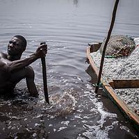 Un homme gratte le fond du lac à l'aide d'une pelle pour récolter le sel.