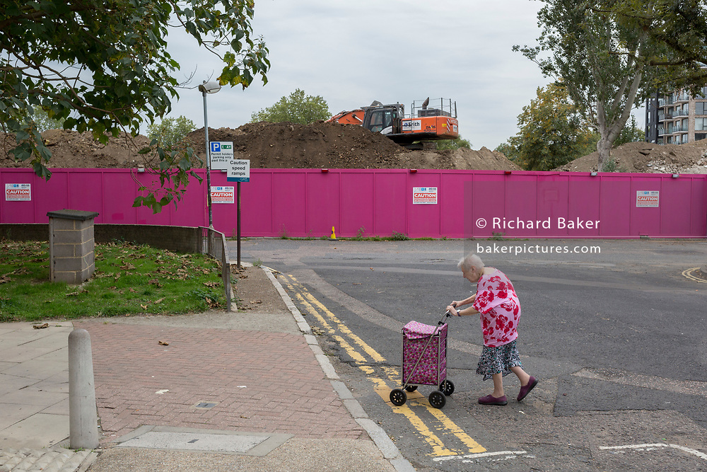 "An elderly lady walks slowly with her shopping trolley across a road on the Aylesbury Estate, on 4th September 2018, in Southwark, London, England. The Aylesbury Estate contained 2,704 dwellings in approximately 7500 residents and built between 1963 and 1977 and for decades it was seen as a symbol of the failure of British social housing. There were major problems with the physical buildings on the estate and the poor perception of estates in Britain as a whole have led to the Aylesbury Estate gaining the title of ""one of the most notorious estates in the United Kingdom. Demolition is in progress for the regeneration of the Aylesbury Estate to consist of 3,500 new homes, 50% of which, according to Southwark council, will be affordable."