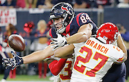 HOUSTON, TX - JANUARY 09:  Ryan Griffin #84 of the Houston Texans drops the ball as he is pressured by Tyvon Branch #27 and Husain Abdullah #39 of the Kansas City Chiefs during the fourth quarter of the AFC Wild Card Playoff game at NRG Stadium on January 9, 2016 in Houston, Texas. The Chiefs won 30-0 over the Texans.  (Photo by Thomas B. Shea/Getty Images) *** Local Caption *** Ryan Griffin;Tyvon Branch;Husain Abdullah