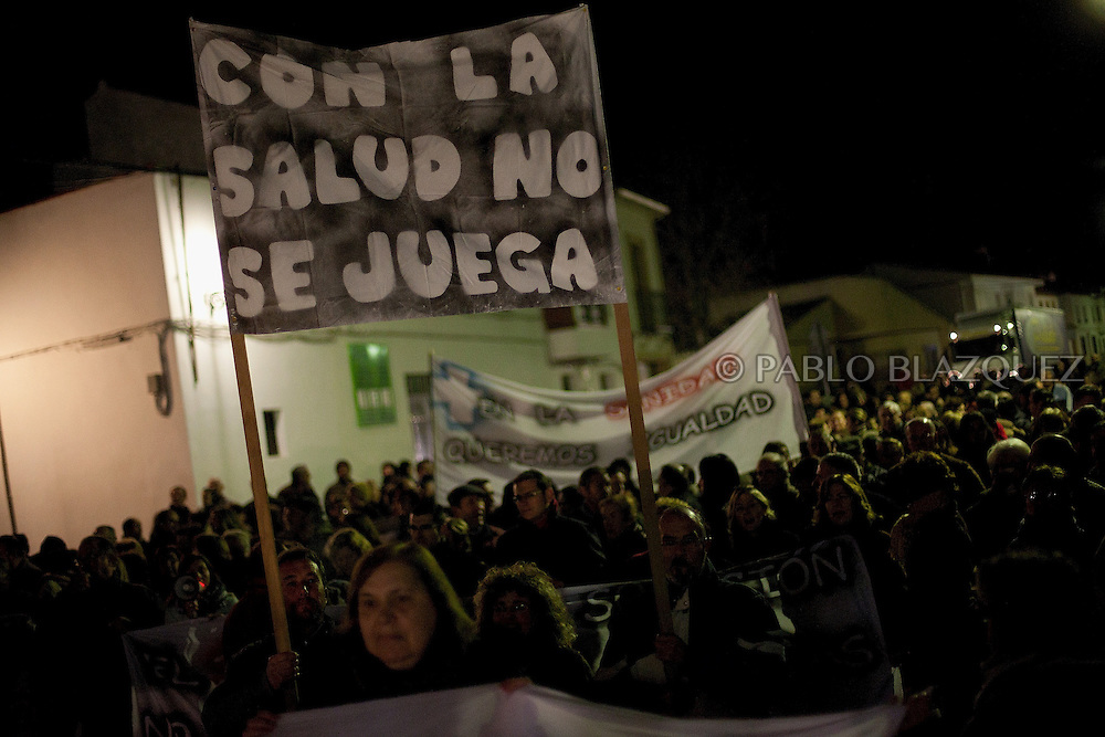 People rally and shout slogans on their way towards the local healthcare centre which closes at 8pm tonight its emergency hours on January 14, 2013 in Tembleque, near Toledo, Spain. Banner reads 'Don't play with health' A total of 21 centres, specially in rural areas, in the region of Castilla-La Mancha, are eliminating emergency hours services following budget cuts and privatisations in Spanish health services.