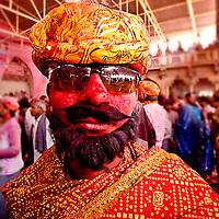 A man with colorful outfit during the Holi Celebration at Barsana. Braj ki Holi
