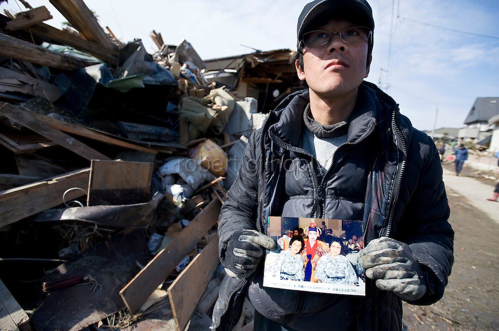 Makoto Takahashi shows a photo of his mother (shown on the left of the photo he is holding) whom he found dead outside the battered remains of their home after the March 11 megatsunamis in Tona, Miyagi Prefecture, Japan on  25 March 20011. .Photographer: Robert Gilhooly