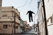 """On a Tripoli street corner, a hanging  human silhouette tells a warning """"to show Gadhafi's forces that their destiny is to be hanged, justifying for the crimes they have being doing against civilians"""" as a rebel fighter claimed it. 26 May 2011."""