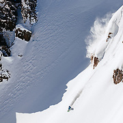 Jess McMillan drops off of extreme terrain in the Teton backcountry outside of Jackson Hole Mountain Resort during a sunny day.