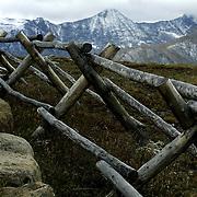 A wooden fence bends along a high mountain meadow in Rocky Mountain National Park near Estes Park, Colorado.