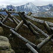 A wooden fence bends along a high mountain meadow in Rocky Mountain National Park near Estes Park, Colorado.