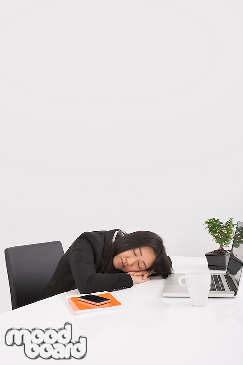 Tired businesswoman resting at desk in office