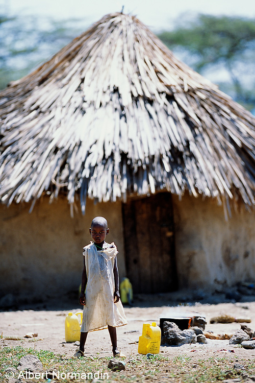 Young girl stands in front of village huts