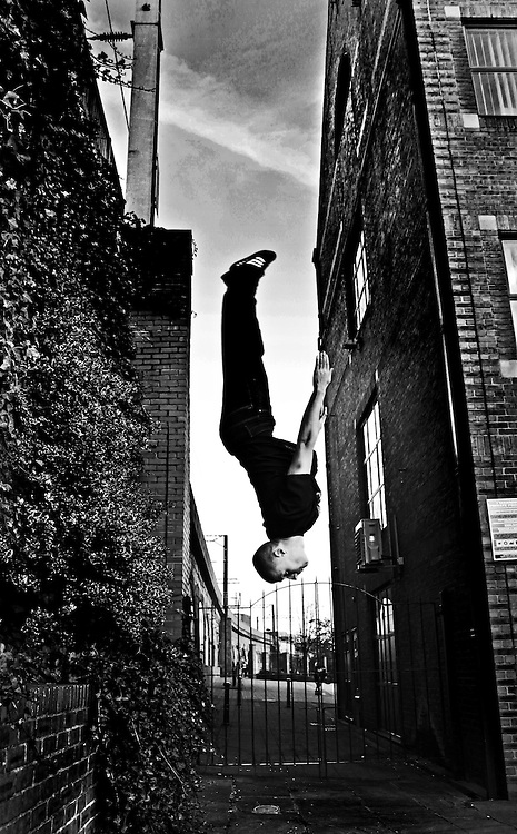 Cheerleader/Tricker/Freerunner Jack Lowry doing a straigh back wall flip in Leeds city centre down by The Calls