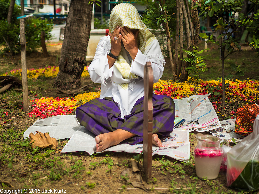 17 JULY 2015 - BANGKOK, THAILAND:     A man prays at a grave in the cemetery of Bang Luang Mosque after Eid services at the mosque in Bangkok. Eid al-Fitr is also called Feast of Breaking the Fast, the Sugar Feast, Bayram (Bajram), the Sweet Festival or Hari Raya Puasa and the Lesser Eid. It is an important Muslim religious holiday that marks the end of Ramadan, the Islamic holy month of fasting. Muslims are not allowed to fast on Eid. The holiday celebrates the conclusion of the 29 or 30 days of dawn-to-sunset fasting Muslims do during the month of Ramadan. Islam is the second largest religion in Thailand. Government sources say about 5% of Thais are Muslim, many in the Muslim community say the number is closer to 10%.          PHOTO BY JACK KURTZ