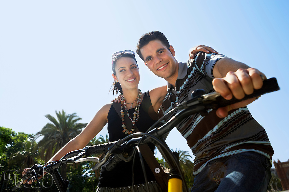 Young couple on bikes portrait low angle view