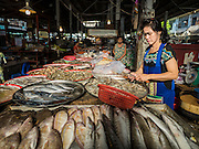 29 JUNE 2015 - BANGKOK, THAILAND:  A fishmonger in the Bang Chak Market. The Bang Chak Market serves the community around Sois 91-97 on Sukhumvit Road in the Bangkok suburbs. About half of the market has been torn down, vendors in the remaining part of the market said they expect to be evicted by the end of the year. The old market, and many of the small working class shophouses and apartments near the market are being being torn down. People who live in the area said condominiums are being built on the land.    PHOTO BY JACK KURTZ