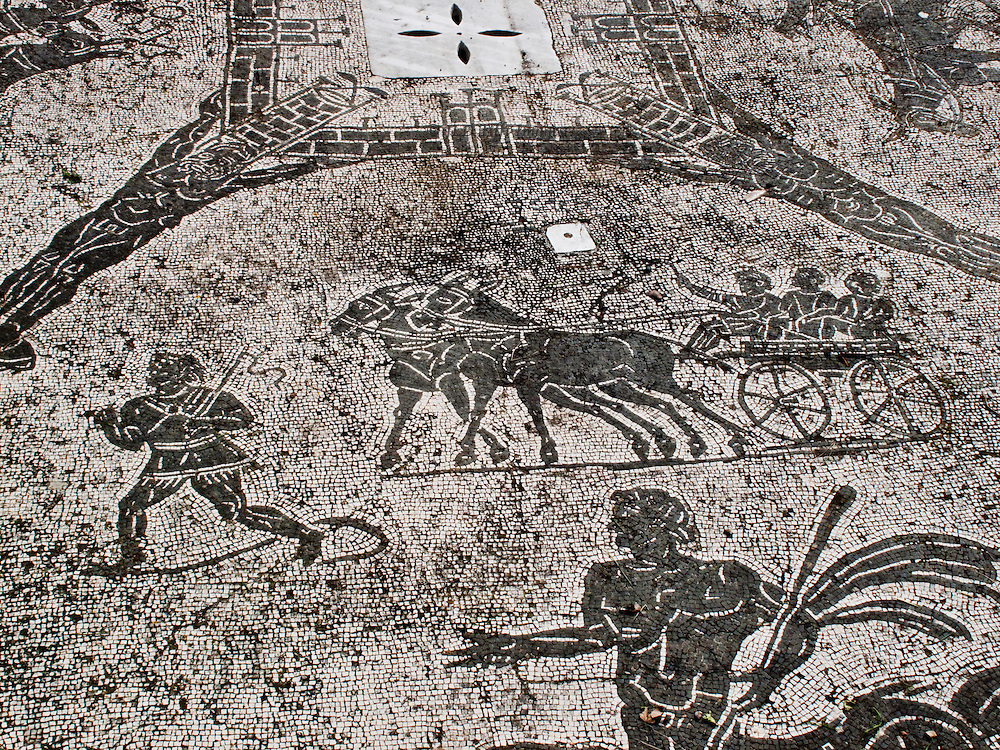 Ostia Antica. Floor mosaic, black and white tesserae, mules drawing a cart filled with children, muleteer carrying whip, partial view of a human-sea monster creature.  Baths of the Coachmen.