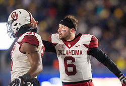 Nov 19, 2016; Morgantown, WV, USA; Oklahoma Sooners quarterback Baker Mayfield (6) celebrates with teammates after the defense recovered a fumble during the second quarter against the West Virginia Mountaineers at Milan Puskar Stadium. Mandatory Credit: Ben Queen-USA TODAY Sports